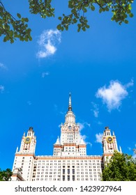MOSCOW, RUSSIA - MAY 27, 2019: green leaves, blue sky and east facade of The Main Building of Moscow State University (Lomonosov State University of Moscow) in sunny summer day