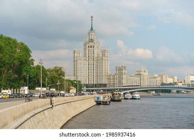 Moscow, Russia - May 27, 2021: Photography of Stalinist skyscraper on Kotelnicheskaya embankment  in spring day. Traffic on the road. Touristic boats on the Moscva river