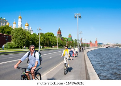 Moscow, Russia - May 27,2018: Moscow cityscape around Kremlin Embankment, with Kremlin on the left hand side, tourists ride bicycles.