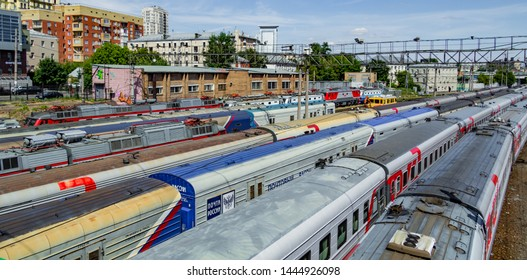 Moscow / Russia - May 29 2018; Russian Railways passenger trains. Passenger train lines. RZD passenger coaches cars. Train coaches and shunter locomotive.