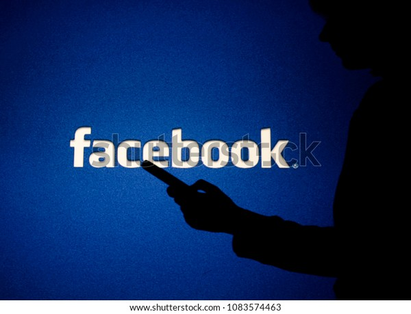 Moscow, Russia - May, 4: A woman looks into the smartphone in front of Facebook logo.