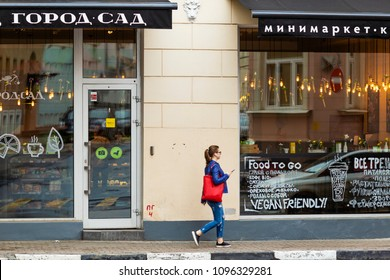 MOSCOW, RUSSIA - MAY 6, 2018: Young woman is walking by vegan friendly cafe in Moscow center. Inscriptions in Russian - City the Garden, Minimarket, coffee, smoothie, juices, rolls, healthy food, etc.