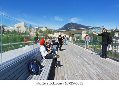 Moscow, Russia - May 7,2018: People on the soaring bridge in Zaryadie park, Moscow, Russia. This V-shaped construction hangs over river and proposed for sightseeing only