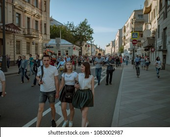 MOSCOW, RUSSIA - MAY 9, 2016: A skinhead with two girls are walking along Bolshaya Ordynka Street after the march Immortal Regiment. Looks at the camera