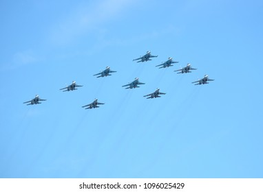 MOSCOW, RUSSIA - May 9, 2018: Group of Russian military supersonic high-altitude interceptors SU-34, SU-35, SU-30SM shows figure Tactical Wing in flight in the blue sky on parade on May 9, 2018