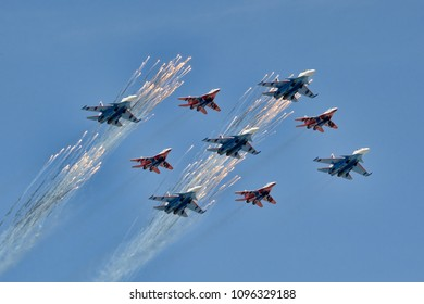 "MOSCOW, RUSSIA - May 9, 2018 Russian Air Force fighters Su-30SM of pilot group ""Russkiye Vityazi"" (Russian Knights) and MiG-29 of ""Strizhi"" (Swifts) aerobatic team shoot flares during Victory Parade"
