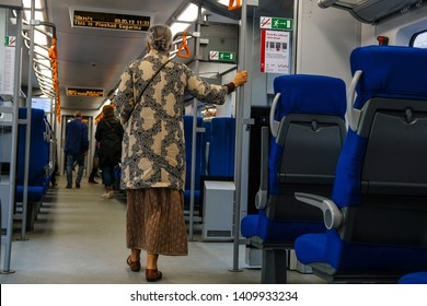 Moscow, Russia - May, 9, 2019: image of an old woman holding a handrail in a subway car