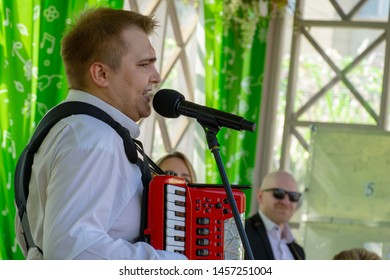 MOSCOW, RUSSIA - MAY 9, 2019: Man in white shirt playing accordion and singing
