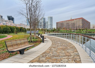 "MOSCOW, RUSSIA - Modern style bench at a pond on a walking path paved with stone tiles in the new urban park ""Khodynka field"" (Khodynskoye pole) in autumn season."