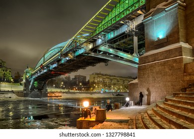 MOSCOW, RUSSIA - Mysterious picture of a young girl in a black winter coat sending a text messages at a pier of Bohdan Khmelnytskyi bridge illuminated in different colors in a dark winter night.