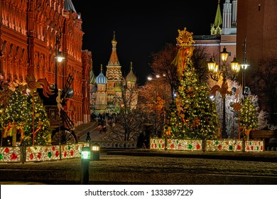 MOSCOW, RUSSIA - Night view of the beautiful illuminated decorations and street lights on Manezhnaya square in the background of St. Basil's Cathedral during Maslenitsa (butter / pancake week) holiday
