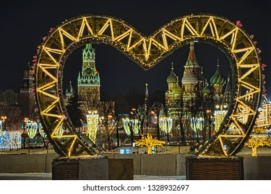 MOSCOW, RUSSIA - Night view of Moscow famous attractions, Kremlin Spasskaya (Savior) tower and St. Basil's Cathedral, framed with heart-shaped lighting installation at Raushskaya emb. of Moskva River.