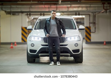 MOSCOW, RUSSIA - NOV 17, 2017: Man (MR) stands leaning on hood of white BMW car standing at underground parking.