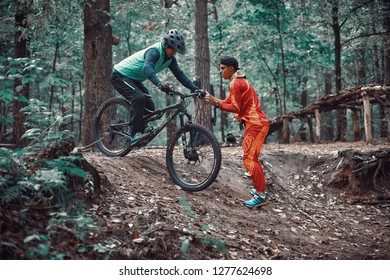Moscow, Russia - Nov, 2018: MTB teacher helping rider learn to ride bicycle. Teaching a rider to ride a bike on a trail.  Two friends have fun in nature and representing concept of fitness on mtb bike