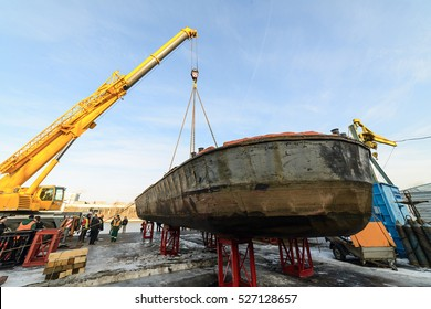 MOSCOW, RUSSIA - NOVEMBER 11, 2016: State Unitary Enterprise Mosvodostok performs recovery vessels on coastal winter parking. The ship is set on the abutments using a truck crane.