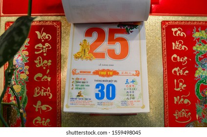 Moscow, Russia, November 2019: Detachable tear-off Vietnamese calendar with date December 25, 2019 on the wall: red numbers, hieroglyphs, beautiful gold background, lunar and solar calendar