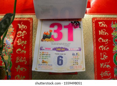 Moscow, Russia, November 2019: Detachable tear-off Vietnamese calendar with new year eve, date December 31 on the wall: red and pink numbers, hieroglyphs, beautiful gold background, lunar and solar
