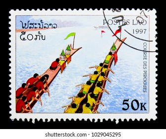 MOSCOW, RUSSIA - NOVEMBER 26, 2017: A stamp printed in Lao People's Democratic Republic shows Team in red shirts, team in yellow shirts rowing upward, Canoe races serie, circa 1997