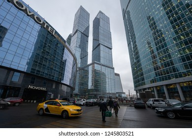 Moscow, Russia - November 27, 2018: People is walking at The Moscow International Business Center territory in the evening. Complex of skyscrapers and a yellow taxi on the road