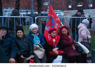 Moscow, Russia, November 7, 2017 - Older people supporters of the communist party are sitting on a bench with communist symbols.