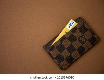 MOSCOW, RUSSIA - OCT 31,2017: Illustrative and Editorial image of Louis Vuitton Card Holder and Gold credit card Visa on Dark Background. Louis Vuitton is a designer fashion brand.