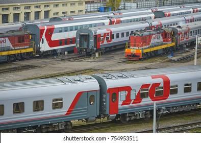 MOSCOW, RUSSIA, OCT,26, 2017: Russian Railways passenger trains in Rizhskaya depot under maintenance. Passenger train lines. RZD passenger coaches cars. Train coaches and shunter locomotive. RZD logo