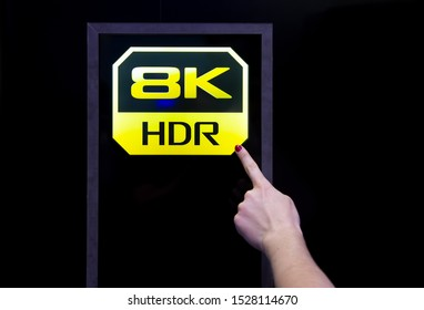 Moscow, Russia - October 04, 2019: female finger points to 8k hdr quality icon. background is black