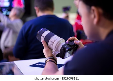 Moscow, Russia - October 04, 2019: men holds new mirror-less camera sony alpha a7 iii 3 with lens sony 70-200 3,28-4,92. soft focus, side view