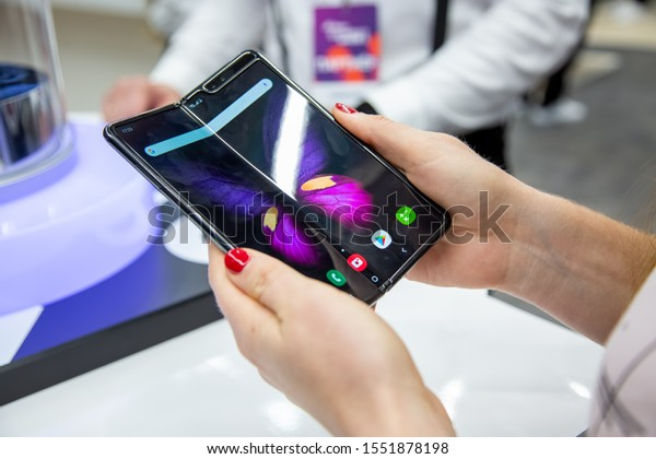 Moscow, Russia - October 04, 2019: female hands holding a new flagship smartphone Samsung Galaxy Fold with flexible display. close up. backgtound in blur