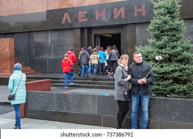 MOSCOW, RUSSIA - OCTOBER 06, 2016: Selfie-taking tourists on the background of the Lenin's Mausoleum (Lenin's Tomb) on the Red Square. The Mausoleum is a resting place of Soviet leader Vladimir Lenin