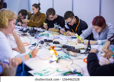 MOSCOW, RUSSIA - OCTOBER 12, 2018: 3D Print Expo - Group of people using 3D printing pens and making plastic models at technology exhibition Future and technology concept
