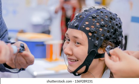 MOSCOW, RUSSIA - OCTOBER 12, 2018: Science Festival - smiling teenager girl with medical eeg headset equipment at technology exhibition. Medicine, neurology and electroencephalography concept