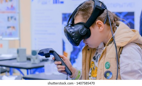 MOSCOW, RUSSIA - OCTOBER 12, 2018: Science Festival - teenager boy using virtual reality headset with controller sticks at futuristic exhibition. Gaming, video game, VR and leisure time concept