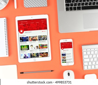 Moscow, Russia - October 13, 2016: Top view on workplace. Iphone and ipad over red background displaying Youtube app. YouTube is the popular online video-sharing website, founded in February 14, 2005