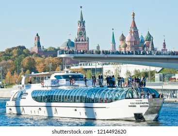 """MOSCOW, RUSSIA - OCTOBER 13, 2018: Radisson Royal Flotilla yacht near  """"floating bridge"""" of park """"Zaryadye"""". Spasskaya Tower and Cathedral of Vasily the Blessed (Saint Basil's Cathedral) on Red Square"""