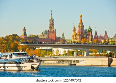"MOSCOW, RUSSIA - OCTOBER 13, 2018: Radisson Royal Flotilla yacht near  ""floating bridge"" of park ""Zaryadye"". Spasskaya Tower and Cathedral of Vasily the Blessed (Saint Basil's Cathedral) on Red Square"