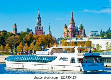 MOSCOW, RUSSIA - OCTOBER 13, 2018:   Spasskaya Tower and Cathedral of Vasily the Blessed (Saint Basil's Cathedral) on Red Square and Radisson Royal Flotilla yacht on Moskva-river in sunny autumn day