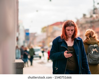 Moscow, Russia - October 19, 2019: A young woman with red hair  in a  blue coat is walking along the street with a mobile phone in her hand. Warm sunny autumn day