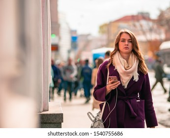 Moscow, Russia - October 19, 2019: A young woman in a purple coat is walking along the street with a mobile phone in her hand and headphones. Warm sunny autumn day