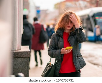Moscow, Russia - October 19, 2019: A young woman in a black coat is walking along the street with a mobile phone in her hand. Warm sunny autumn day