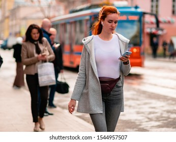 Moscow, Russia - October 19, 2019: A young woman in a white coat is walking along the street with a mobile phone in her hand and headphones. Warm sunny autumn day