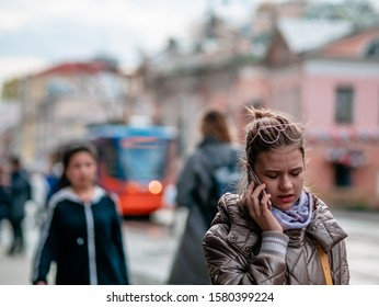 Moscow, Russia - October 19, 2019: A young woman in a light coat is walking along the street with a mobile phone in her hand and talking. Warm sunny autumn day