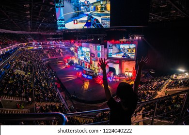 MOSCOW, RUSSIA - OCTOBER 2018: Counter Strike: Global Offensive esports event. Happy girl fan on a tribune at arena with a hands raised.