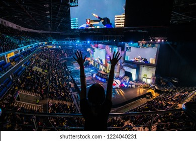 MOSCOW, RUSSIA - OCTOBER 2018: Counter Strike: Global Offensive esports event. Happy girl fan on a tribune at arena cheering for her favorite team. Hands raised