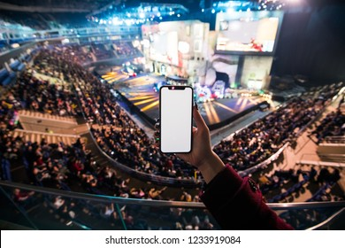 MOSCOW, RUSSIA - OCTOBER 2018: Counter Strike: Global Offensive esports event. Woman's hands using digital application on the mobile smart phone at esport event at big arena.