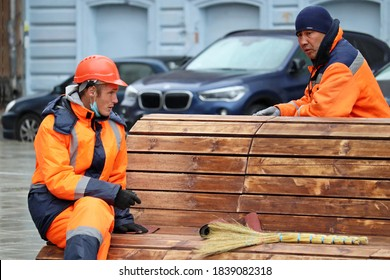 Moscow, Russia - October 2020: Public utilities workers sitting on the wooden bench. Janitors in Moscow, street cleaning, concept of unskilled job