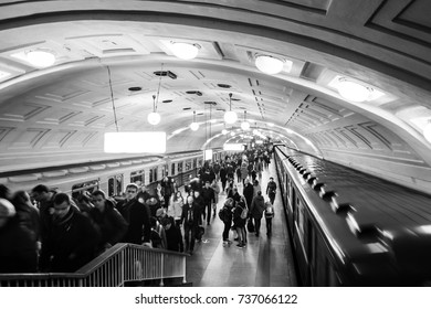MOSCOW, RUSSIA - OCTOBER 23, 2016: Inside a Lenin Library metro station at rush hour in Moscow, Russia. Unidentified people at the platform with moving trains. Black and white