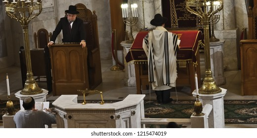 Moscow / Russia- October, 25, 2018:  the rabbi prays with the holy of holies, he is dressed in tallit (tallit) and has his back turned, candles. the second rabbi looks strictly at the believers.