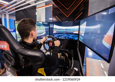 MOSCOW, RUSSIA - OCTOBER 27 2018. Simulation of race car video player game with big screen monitors and cockpit controls like a racing car.
