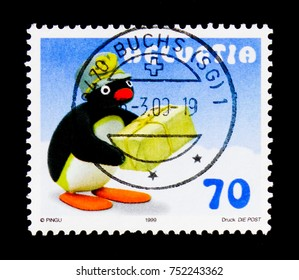 MOSCOW, RUSSIA - OCTOBER 3, 2017: A stamp printed in Switzerland shows Pinguin as postman, Pingu Comics Character serie, circa 1999